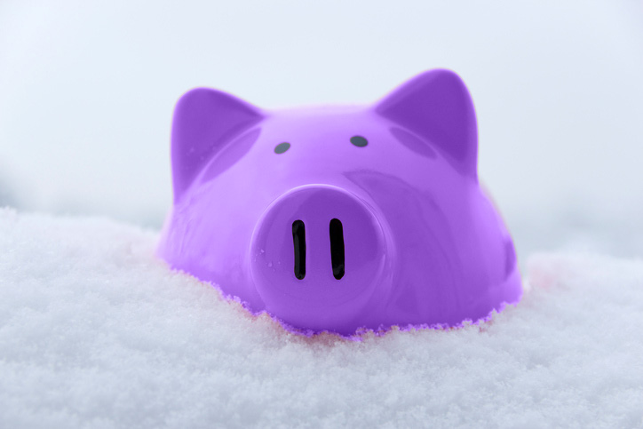 Purple piggy bank in snow